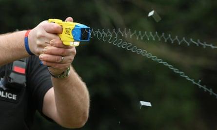 A police officer using a Taser.