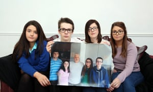 Siobhan McLaughlin (2nd right) with three of her four children and holding photo of her late partner John Adam with all their children.