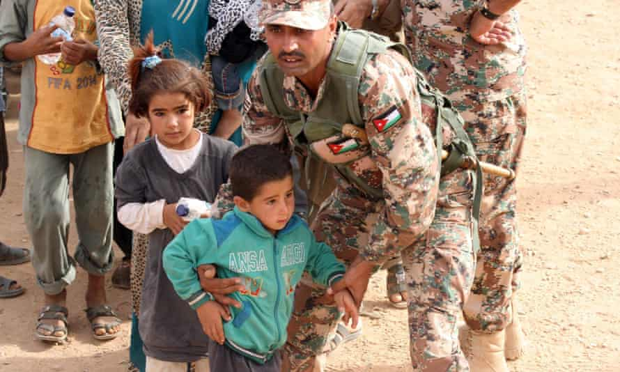 A Jordanian soldier helping Syrian children on their arrival at the border in September 2015.