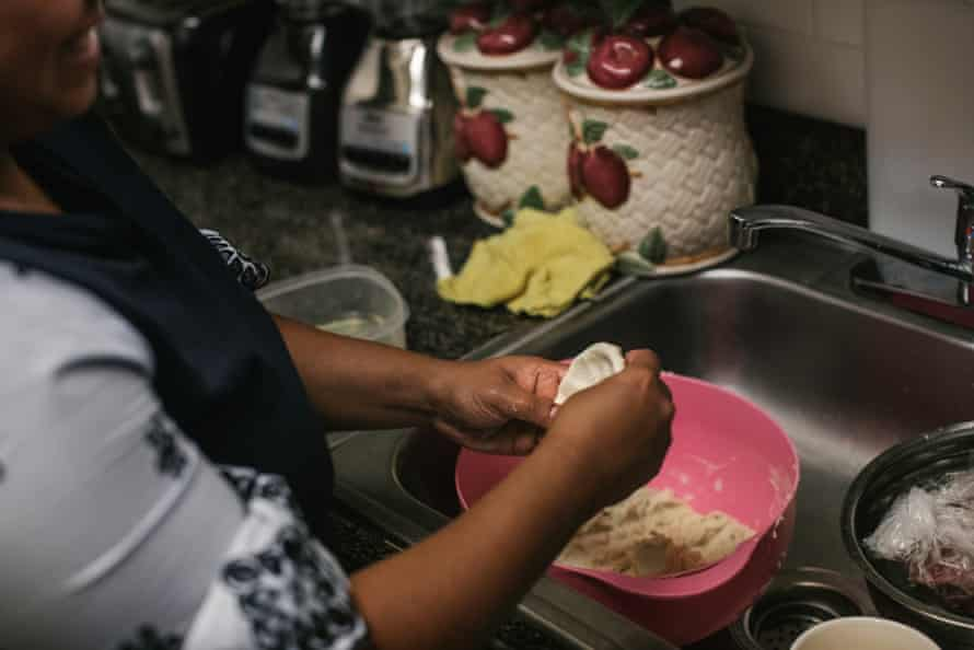 Carmen makes pupusas for lunch at her mother's home while her brother José waits with family in the living room.