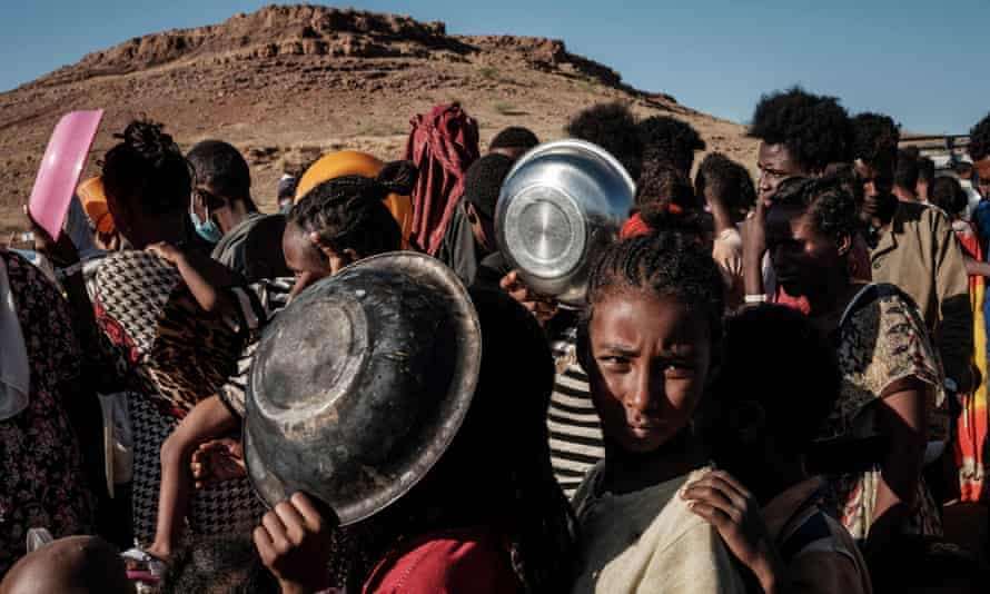 Ethiopian refugee children who fled the Tigray conflict wait in a line for a food distribution by Muslim Aid at the Um Raquba refugee camp in Sudan.