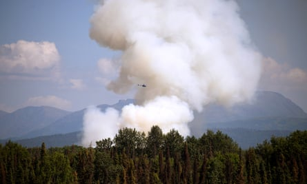 A helicopter passes by as smoke rises from a wildfire on 3 July south of Talkeetna, Alaska.