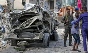 Security forces stand near the wreckage of an official vehicle destroyed in the first of Saturday's bomb attacks, in Mogadishu.