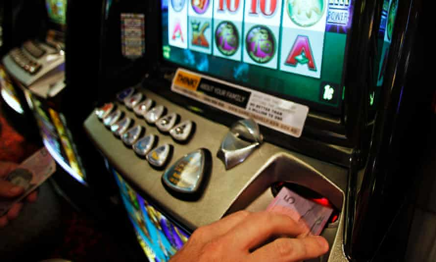 File photo of a man inserting a $5 note into a poker machine