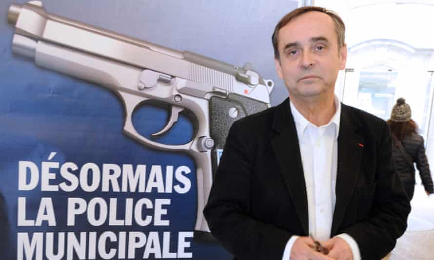 Robert Ménard poses in front of a municipality campaign poster showing a handgun