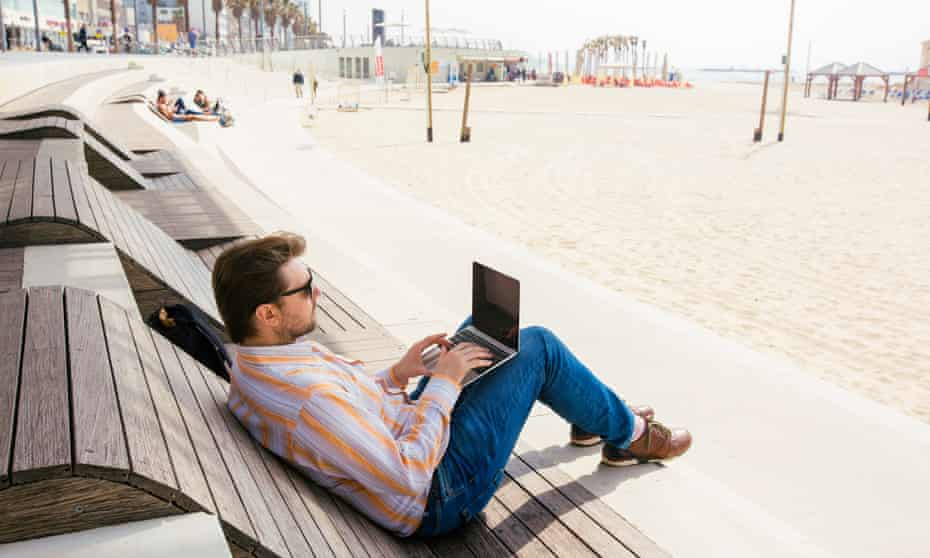 Man working on a laptop on the beach.