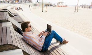 A man types on his laptop on a beach in Tel Aviv.