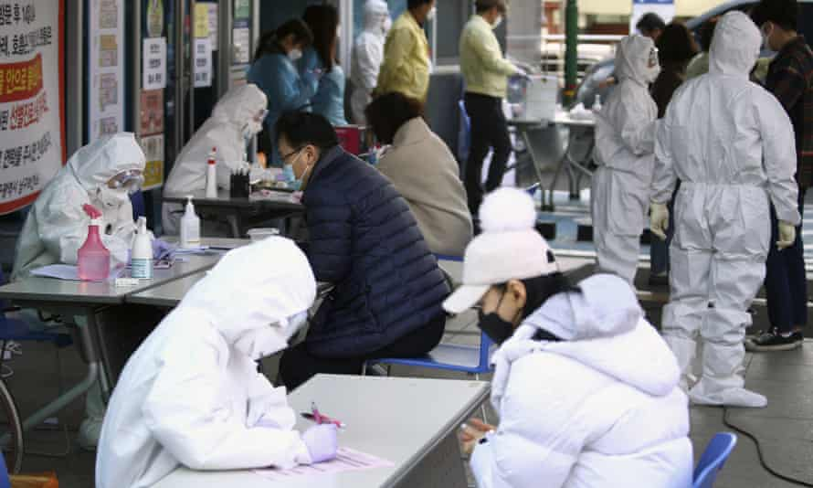 Coronavirus outbreak: workers take details from people suspected of having Covid-19 at a temporary medical centre in Daegu, South Korea.
