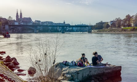 People sit on a concrete slab at the edge of the River Rhine in Basel with a view of the city skyline. Switzerland.