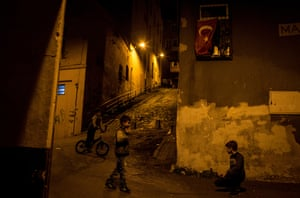 Children play under a Turkish national flag on a street in the Kasimpasa neighbourhood of Istanbul, Turkey