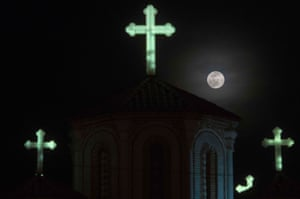 The moon rises over a chruch in Skopje, North Macedonia
