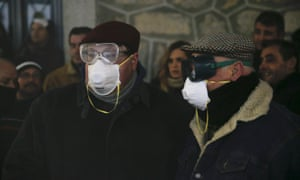 Some of the watching crowds wear masks to protect themselves from the smoke