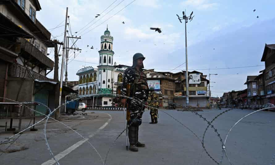 Security personnel stand guard on a street in Srinagar.