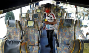 A man disinfects seats of an air-conditioned passenger bus after Gujarat state authorities resumed the bus services after easing lockdown restrictions in Ahmedabad, India.