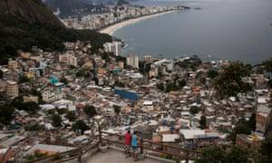 Men overlook the city from the Vidigal favela, in Rio de Janeiro, Brazil.