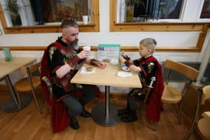 People dressed in Viking costumes have breakfast