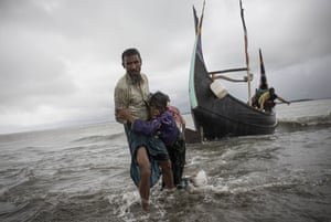 A Rohingya man carries an elderly woman, after the wooden boat they were travelling on from Myanmar, which can be seen in the background, crashed into the shore and tipped everyone out
