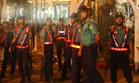 Policemen stand guard after a series of blasts targeting a Shia Muslim gathering in Bangladesh.