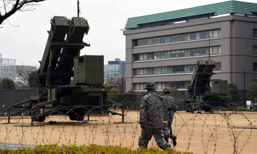 Soldiers walk beside PAC-3 missile launchers on the grounds of the defence ministry in Tokyo on January 30, 2016.