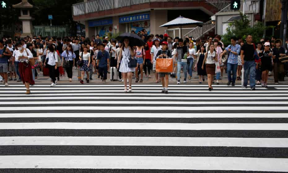 People walk on a crosswalk at a shopping district in Tokyo, Japan.