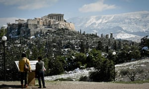 Women look at an information board at the Pnyx hill in central Athens, while the remains of heavy snowall cover the Acropolis and nearby hills in Athens on February 17, 2021.