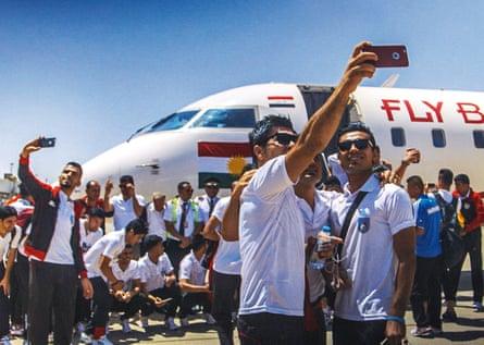 Members of the Kurdistan football team taking selfies at Irbil airport
