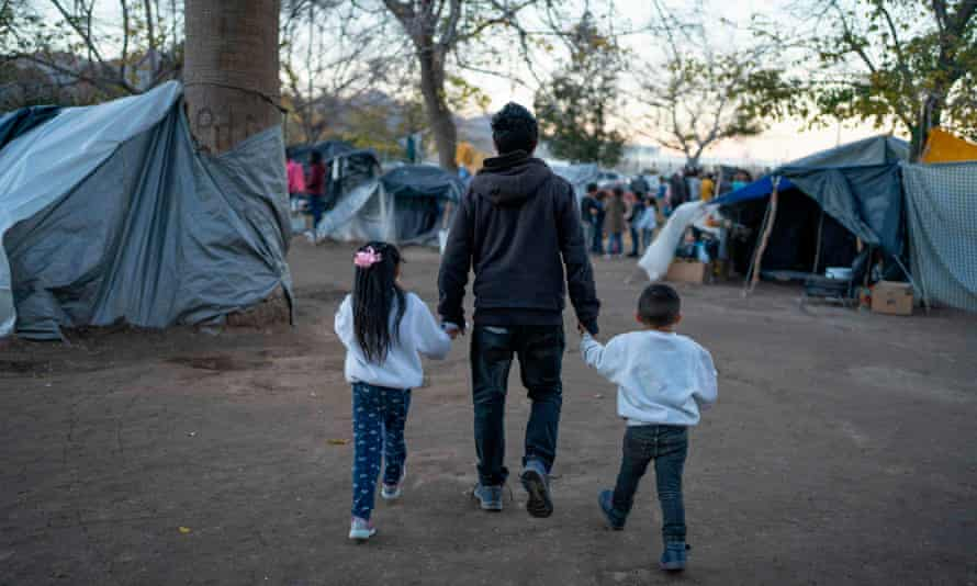 A man and his children through a campsite of Mexican asylum seekers in Ciudad Juarez. Mexican literary figures say their criticism of American Dirt has been silenced.