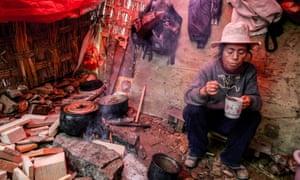 A woman eats food at her shelter in San Juan de Miraflores district of Lima, Peru