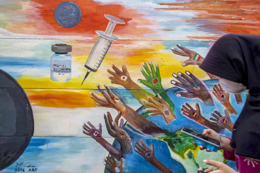 A woman passes a Covid vaccine mural in Tangerang, Banten, Indonesia.
