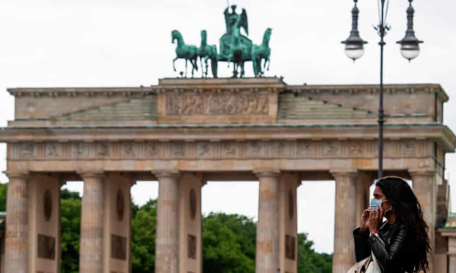 A woman puts on a face mask in front of the Brandenburg Gate