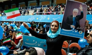 An Iranian supporter of the reformists holds up a picture of parliamentary candidate Mohmmad Reza Aref in one hand and a flag of the Islamic Republic in the other.