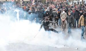 A protestor kicks a tear gas cannister