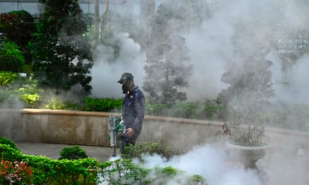 A mask-clad worker disinfects an area in Taipei.