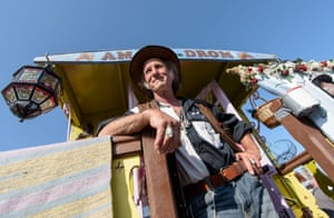 A Gypsy stands in front of his folklore wagon