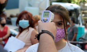 A student gets her temperature checked before attending school in Athens on Monday.