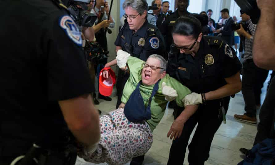 Capitol police carry out a demonstrator protesting outside Mitch McConnell's office.