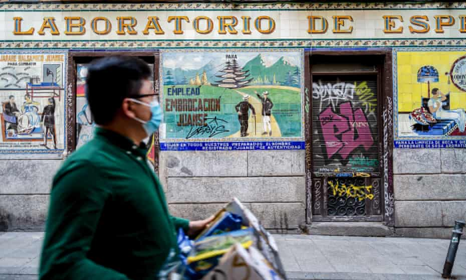 A man walks past a closed bar in the Malasaña district of Madrid