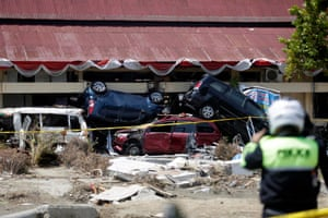 Numerous automobiles are piled on top of each other after a structure collapsed during the earthquake.