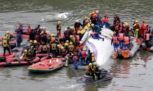 Rescuers carry out rescue operations after a TransAsia plane crashed into a river in New Taipei City.