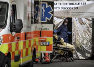 A woman on a stretcher is carried out of an ambulance into a tent set up by the Italian Civil Protection next to the emergency ward of the Piacenza hospital, northern Italy.