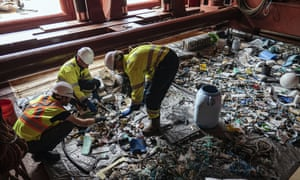 Crew members sort through plastic onboard a support vessel in the Pacific.