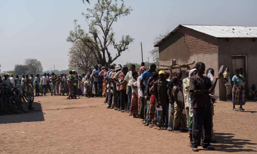 People stand in line for food aid