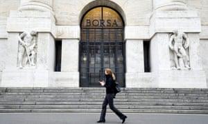 A woman walking past the Italian stock exchange in Milan.