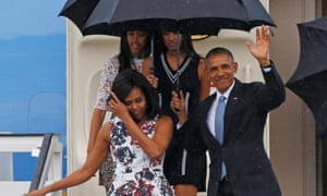 The Obamas wave to onlookers at the airport.