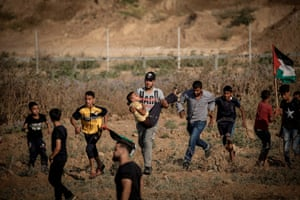 Palestinians on the Gaza Strip evacuate a wounded demonstrator during a protest along the border with Israel near Bureij.