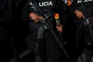 A female police officer from the new police tactical unit holds a rose on Valentine's day in San Salvador.