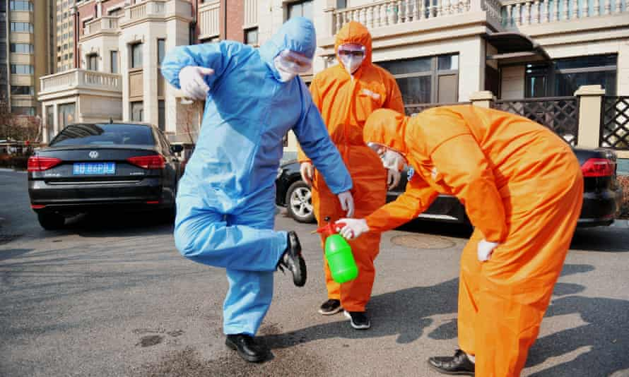 A member of the team of coronavirus control disinfects the shoes of a co-worker after a visit to an isolated family in Qingdao in east China's Shandong province.