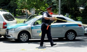 An officer wraps up police tape at a street in Almaty, Kazakhstan.