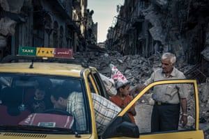 Homs, June 2014: Abu Hisham Abdel Karim and his family bundle salvaged possessions into a taxi.