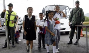 Children walk past Venezuelan soldiers, across the border, over the Francisco de Paula Santander international bridge to attend school in Colombia.